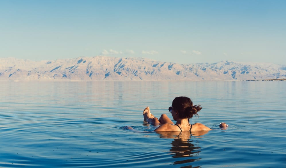 Girl is relaxing and swimming in the water of the Dead Sea in Israel, Best Time to Visit Israel